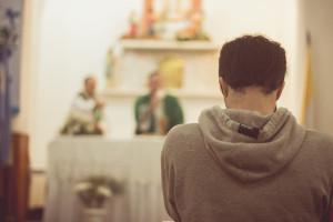 Jeune homme participant à la célébration de l'eucharistie.