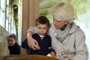 23 avril 2014 : Une grand-mère faisant le signe de croix avec son petit-fils de 3 ans, cloître de la basilique de Vézelay. Vézelay (89), France.