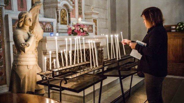 9 octobre 2016 : Trois mois après l'attentat de Nice, une fidèle catholique dépose un cierge avant la messe dominicale en l'église St Pierre d'Arène, située aux abords de la promenade des Anglais. Nice (06), France.