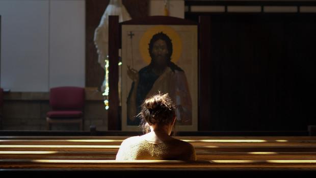 Jeune fille en prière dans une église.