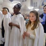 26 mars 2016 : Les nouveaux baptisés sont revêtus du vêtement blanc et portent la lumière pascale, lors de la célébration de la Vigile pascale. Paroisse Saint Ferdinand des Ternes, Paris (75), France.