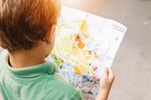 Un petit garçon lit une carte.