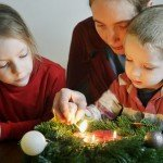 22 novembre 2014 : Illustration du temps de l'Avent. Une mère et ses enfants allument les bougies, d'une couronne de l'Avent. Paris (75), France.
