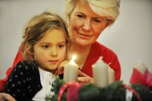 1er décembre 2013 : Transmission de la foi. Illustration du temps de l'avent. Une grand-mère et sa petite fille allument la première bougie, d'une couronne de l'avent. Paris (75), France.