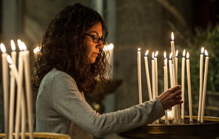 31 mars 2015 : Une jeune femme allume un cierge lors de la prière en mémoire des martyrs contemporains célébrée en la basilique Sainte-Marie-du-Trastevere, Rome, Italie. March 31, 2015: A young woman lays a candle symbolizing a martyr during a prayer for the Christian martyrs of the XXI century. Basilica of Santa Maria in Trastevere in Rome, Italy.