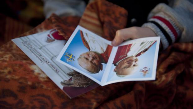 27 avril 2014 : Ambiance sur la place Saint-Pierre où les pèlerins attendent  le début de à la cérémonie de canonisation des papes Jean XXIII et Jean-Paul II. Un pèlerin tient à la main une image sur laquelle se trouvent les portraits des deux papes.