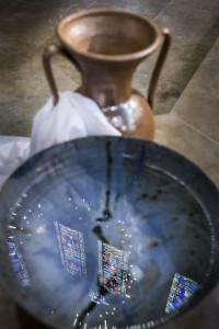 9 mai 2018 : Illustration du baptême, reflet de vitraux dans une cuve baptismale remplie d'eau bénite. Paris (75), France.