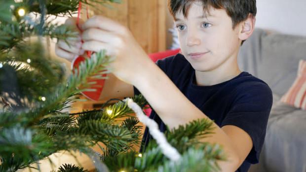 13 décembre 2017 : Garçon de 10 ans décorant un sapin de Noël. France.