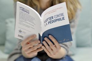 """25 janvier 2017 : Femme lisant la brochure """"Lutter contre la pédophilie"""", éditée par la Conférence des Evêque de France (CEF). Paris (75), France."""