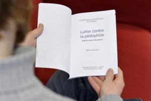 """25 janvier 2017 : Homme lisant la brochure """"Lutter contre la pédophilie"""", éditée par la Conférence des Evêque de France (CEF). Paris (75), France."""