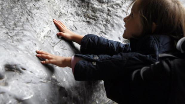 Une enfant touche la paroi de la grotte de Massabielle, Lourdes (65), France.
