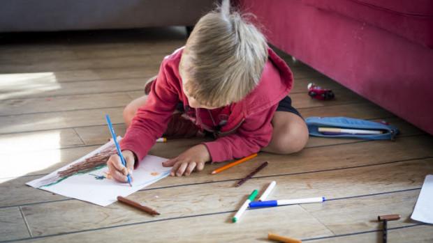 20 octobre 2018 : Illustration. Petit garçon dessinant, assis sur le sol de la maison. France.