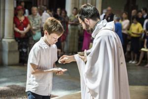 23 juin 2019 : Première communion d'un jeune garçon, lors de la messe célébrée en l'église Saint Jean Baptiste de Belleville. Paris (75), France.