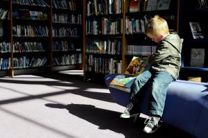 Un petit garçon parcourt un livre illustré dans une bibliothèque municipale.