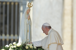 13 mai 2015 : Le pape François touchant la statue de Notre Dame de Fatima lors de l'audience pontificale hebdomadaire sur la place Saint Pierre au Vatican.