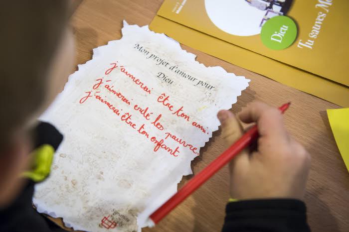 """20 novembre 2018 : Séance de catéchèse d'un groupe de CE1, à la paroisse Saint-Ambroise. Les enfants rédigent leur """"projet d'amour pour Dieu"""". Paris (75), France."""